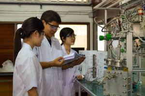 17838527 - male medical or scientific researcher teaching female researchers about an apparatus in a laboratory.